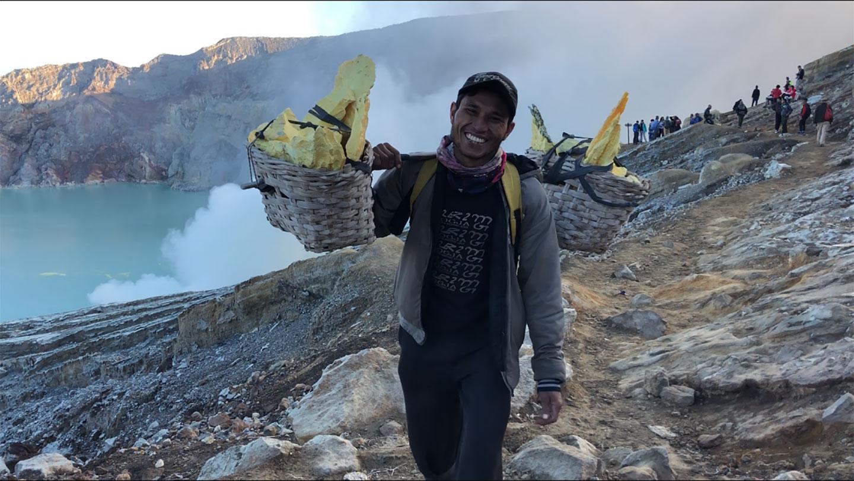 Mijnwerker met manden gevuld met zwavel op Mount Ijen